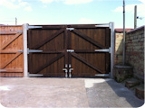 Overweight man walking in front of arched top timber double entrance gates made to measure for a house in Manchester.