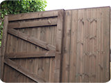 Wooden double garden gates with extra braces to align with existing wall hinge pins.
